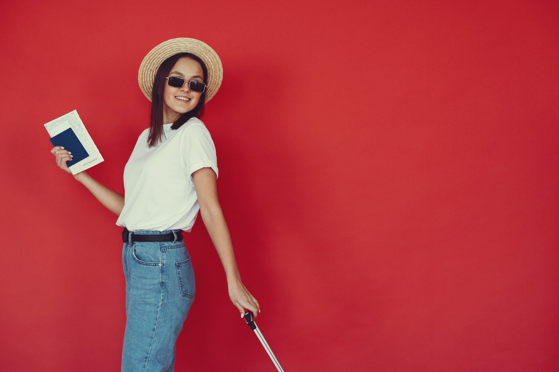 smiling young female with luggage and passport on red background